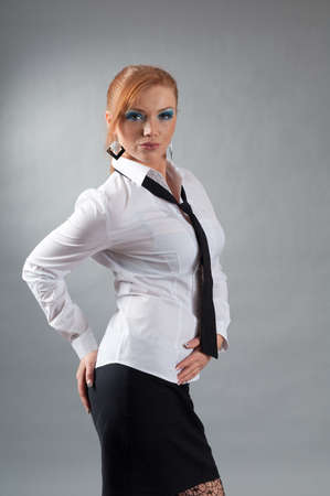 redheaded girl  in formal dress like a secretary with white shirt and tie  photo