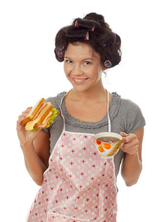 sexy housewife drinking tea with sandwich. Studio, white background.  photo