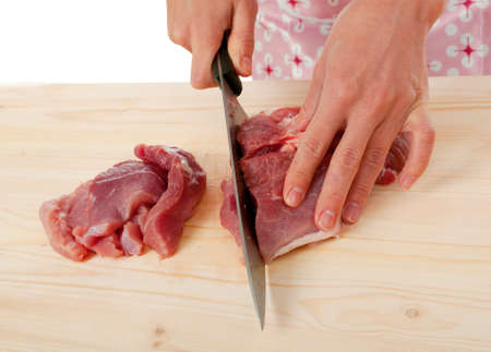 housewife cutting beef on a wooden board . Studio, white background.  photo