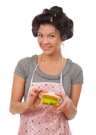 Beautiful cooking woman eat sandwich.Studio, white background.  Stock Photo - 9167597