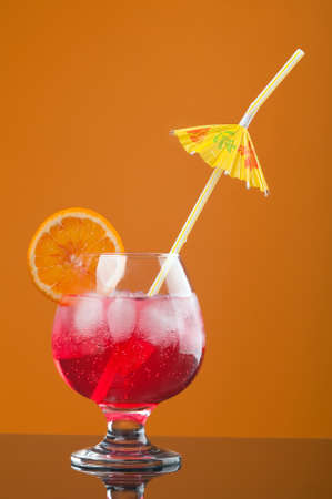 red coctail drink with ice cubs  on yellow background  Stock Photo