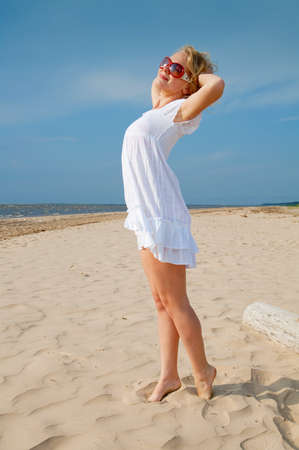 Young woman in summer dress standing on sand photo