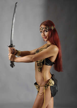 traditional weapon: young warrior woman holding sword in her hand Stock Photo