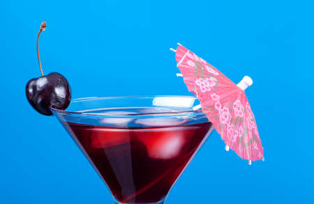 cocktail  with cherry closeupon blue background.
