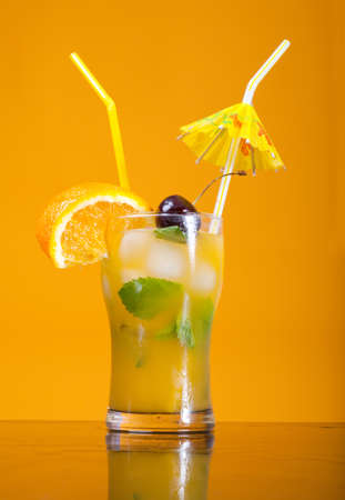 tropical cold cocktail closeup on yellow background.