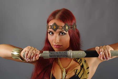 espadas medievales: mujer joven guerrero sosteniendo la espada en la mano Foto de archivo