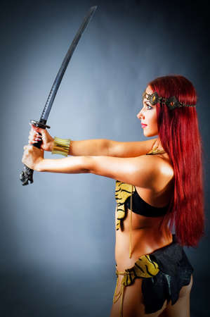 young warrior woman holding sword in her hand photo