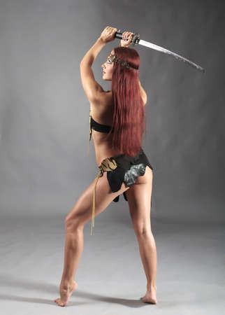 warrior girl: young warrior woman holding sword in her hand Stock Photo