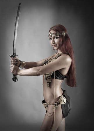 mujer pirata: mujer joven guerrero sosteniendo la espada en la mano Foto de archivo