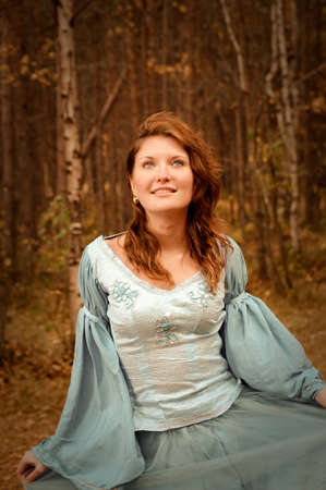 Very beautiful girl in medieval dress in autumn wood photo