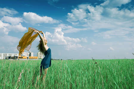happy woman on green grass on background of the town buildings photo
