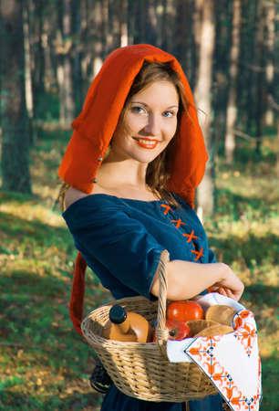 middeleeuwse jurk: Roodkapje staan in een bos. mooi meisje in middeleeuwse kleding