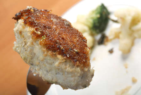Cutlets in a plate with vegetables.Close-up .fork with chop photo