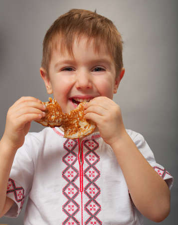 Russian little boy eats pancakes with red caviar. photo