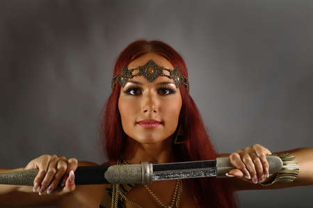 woman with sword: young warrior woman holding sword in her hand Stock Photo