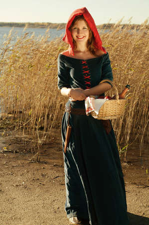 medieval dress: caperucita roja de pie al lado del lago. hermosa chica en vestido medieval Foto de archivo