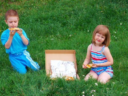 Picnic on the grass. boy and small girl  have a dinner with pizza on the meadow . photo