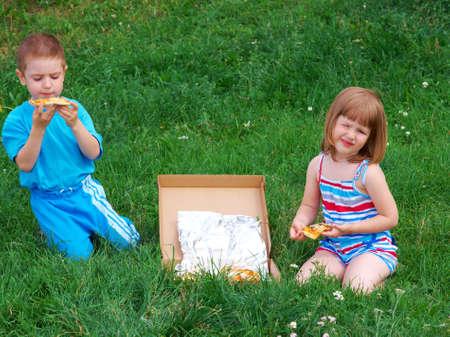 Picnic sull'erba. ragazzo e una ragazza piccola una cena con pizza sul prato.