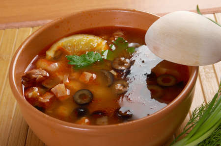 solyanka: Solyanka on the plate.Solyanka, Russian soup with beef,sausage,chicken and lemon, olives Stock Photo