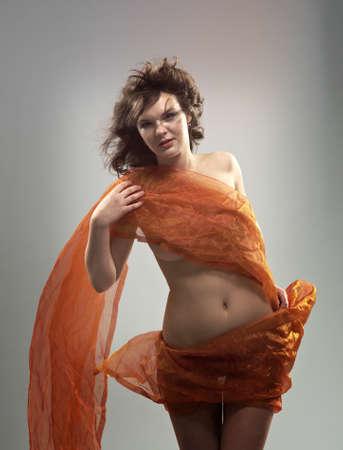 Beautiful woman in  waving fabric.Portrait of young dancing girl photo