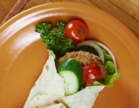 Pita Sandwich with meat,parsley,and tomato sauce photo