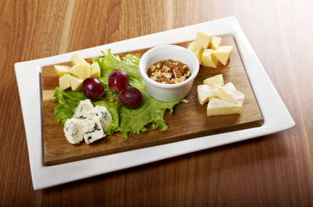 Various types of cheese on wooden platter photo