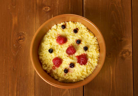 Millet porridge with berry in brown bowl on table Stock Photo