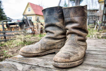 old farmer: old muddy farmers boots on wooden wall