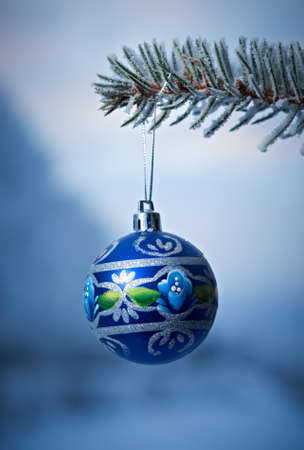 branche sapin noel: bright Christmas bauble from a snow covered Christmas Tree Branch  Banque d'images