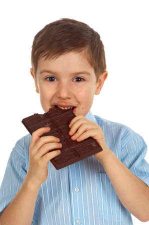 Smiling  funny young kid eating chocolate.White isolated Stock Photo