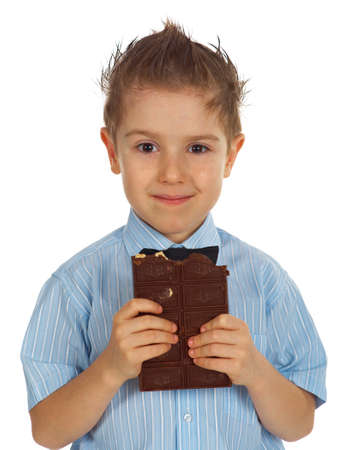 Smiling young kid eating chocolate Stock Photo