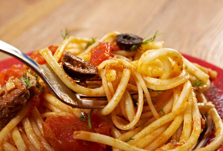 puttanesca: Spaghetti alla puttanesca  salty Italian pasta dish.ingredients are typical of Southern Italian cuisine: tomatoes, olive oil, olives, capers and garlic. Stock Photo