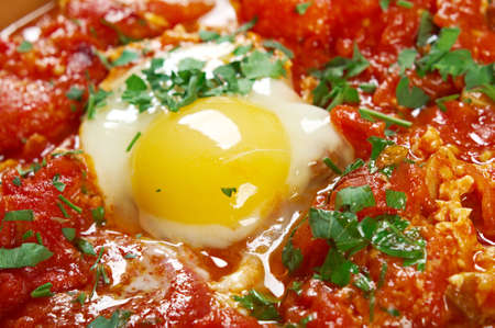 Shakshuka -dish of eggs poached in a sauce of tomatoes, chili peppers, and onions, often spiced with cumin.Moroccan, Tunisian, Libyan, Algerian, and Egyptian cuisines traditionally