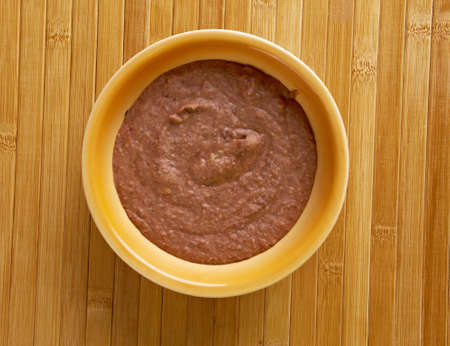 pinto beans: Refried beans dish of cooked and mashed beans and is a traditional staple of Mexican and Tex-Mex cuisine Stock Photo