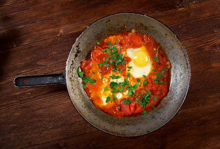 Shakshuka-料理卵の半熟トマト、唐辛子とクミンがしばしば添えられた玉ねぎのソースで。モロッコ、チュニジア、リビア、アルジェリア、エジプト料理伝統的 写真素材 - 27161791