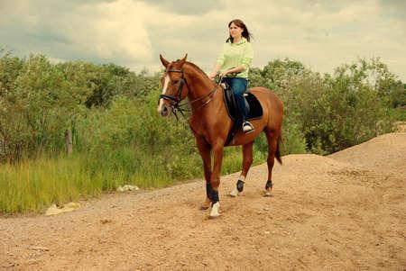 Girl -a jockey  on riding horse .girl horseback on jumps  photo