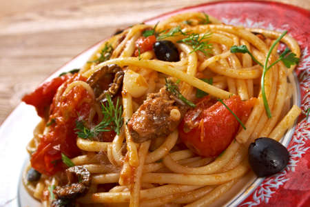 homestyle: Spaghetti alla puttanesca  salty Italian pasta dish.ingredients are typical of Southern Italian cuisine: tomatoes, olive oil, olives, capers and garlic. Stock Photo