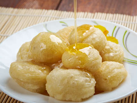 zeppole: Loukoumades Greek pastry made of deep fried dough soaked in sugar syrup or honey and cinnamon Stock Photo