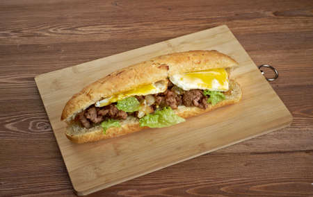 combining: Cheesesteak - sandwich combining frizzled beef, onions, and cheese in a small loaf of bread