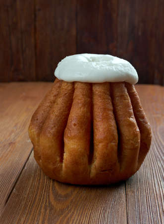 hard liquor: Rum baba  on wooden background. cake saturated in hard liquor, usually rum, and sometimes filled with whipped cream or pastry cream. Stock Photo