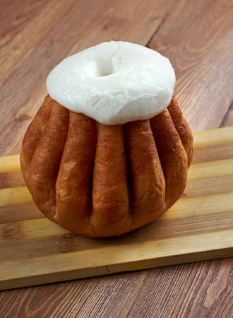 Rum baba  on wooden background. cake saturated in hard liquor, usually rum, and sometimes filled with whipped cream or pastry cream. Stock Photo