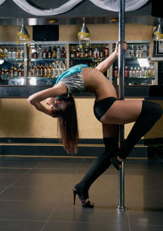 striptease in night club .Young slim pole dance woman photo