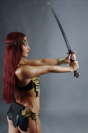 antique woman: young warrior woman holding sword in her hand Stock Photo