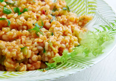 cuisines: Kısır - traditional side dish in Turkish cuisines. main ingredients are finely ground bulgur, parsley, and tomato paste. Stock Photo