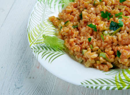tomato paste: Kısır - traditional side dish in Turkish cuisines. main ingredients are finely ground bulgur, parsley, and tomato paste. Stock Photo