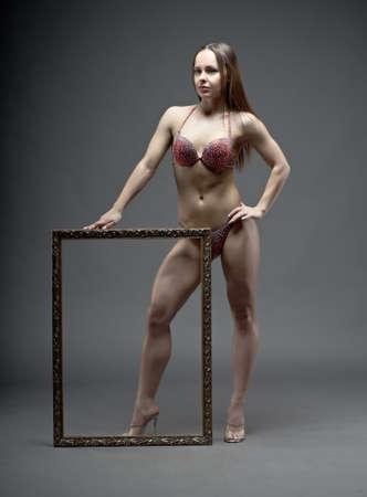 studio b: Woman with perfect athletic body in fitness bikini