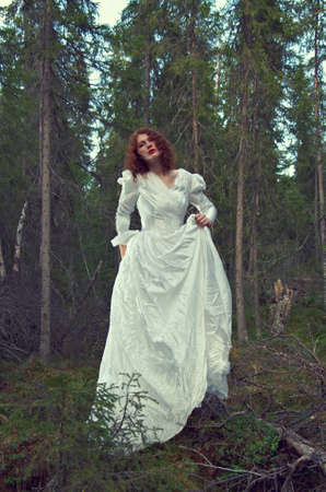 mystical forest: Young woman in white long dress in the mystical forest.