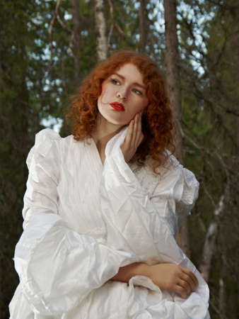 priestess: Young woman in white long dress in the mystical forest.