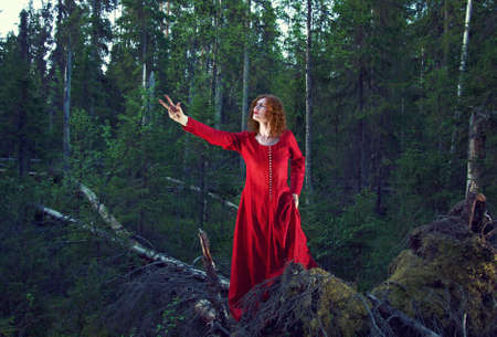 mystical forest: Young woman in red dress in the mystical forest. Stock Photo
