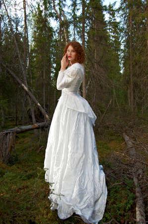 Giovane donna in abito lungo bianco nella foresta mistica.